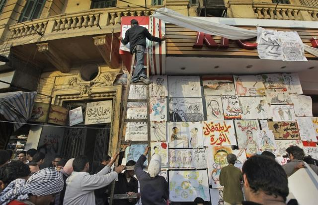 Egyptian activist on ladder at KFC.  Graphics exhibition during protests.